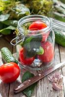 grönsaker och örter i glasburk för hem konservering. foto