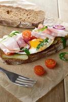 bacon och stekt äggöppen smörgås foto