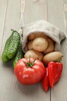 nyskördade organiska grönsaker på träbord foto