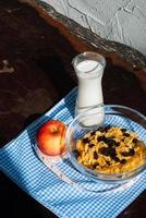 hälsosam frukost: cornflakes, äpplen, russin med mjölk foto