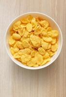 gula majsflingor i vit skål på foto