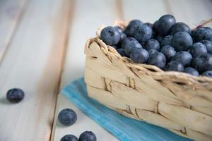 färska blåbär i korg på köksbordet foto