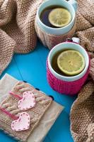 två blå kopp te i stickad tröja med hjärtan