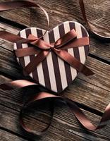 hjärtformade alla hjärtans dag presentförpackning på träplattor. foto