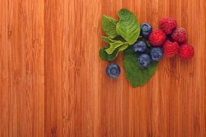 skärbräda med blåbär, hallon och myntablad foto