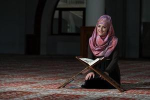 muslimsk kvinna läser koranen foto