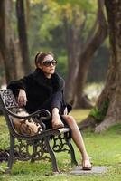 vacker asiatisk dam i svart klänning, poserar i parken foto