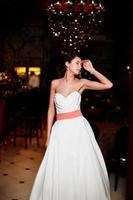 brudbrunettkvinna i vit bröllopsklänning foto