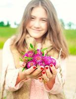 naturens skönhet. le ung flicka håller äng klöver blommor foto