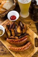 grillade korvar med rostad potatis med kryddor foto