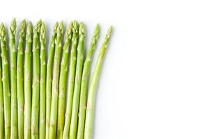 grön sparris till vänster om vit bakgrund foto