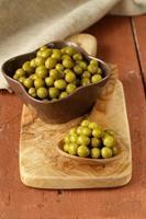 konserverade gröna ärtor i en träsked foto