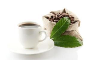 säck full kaffebönor med gröna blad kaffekopp foto