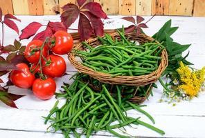 korg med gröna bönor med vita tomater foto