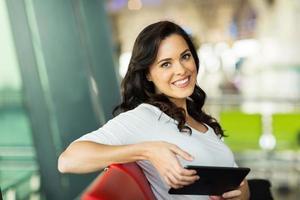 ung kvinna med surfplatta på flygplatsen foto