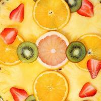skivad fruktbakgrund. jordgubbar, kiwi, ananas, grapefrukt, apelsin foto