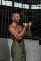 mogen kroppsbyggare som utövar biceps foto