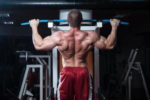 unga kroppsbyggare som gör tungvikt mot rygg foto