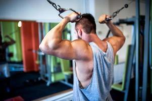 ung, muskulös man, kroppsbyggare som tränar i gymmet. fitness con foto