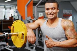 viktlyftare lutar sig på skivstång i gymmet foto