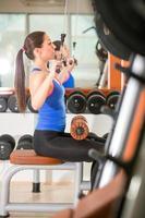 kvinna som tränar på maskin för bodybuilding foto