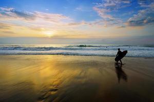 surfer som kommer in i vattnet vid solnedgången foto