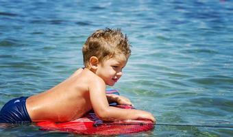 barn har kul på surfbrädan i havet foto