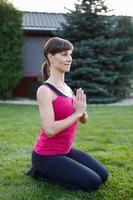 ung brunett sportig kvinna som utövar yoga foto