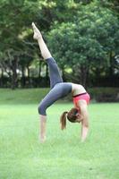 ung vacker kvinna yoga instruktör gör hjul poserar med en foto