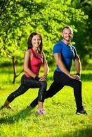 man och kvinna gör stretchövningar foto