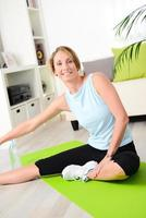 attraktiv och frisk ung kvinna som gör träningsövningar hemma foto