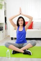 glad ung brunettkvinna som gör yogaövningar hemma foto