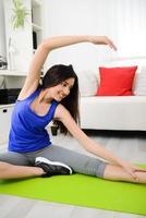 glad ung brunettkvinna som gör fitnessövningar hemma foto