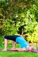 ung kvinna i naturen som gör yoga foto