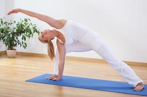 kvinna gör avancerad yogaövning foto