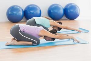 två kvinnor i meditation poserar på fitnessstudio foto