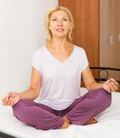 mogen kvinna som utövar yoga foto