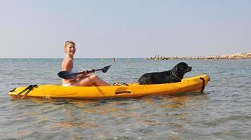 kvinna och hund på en kajak foto