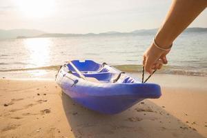man drog kajakken upp på stranden foto
