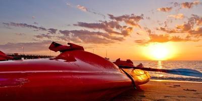 röd kajak på stranden vid soluppgången foto