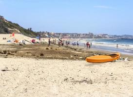 orange kajak på stranden. människor kopplar av, spelar i våt sand, foto