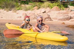 små bedårande flickor som njuter av kajakpaddling