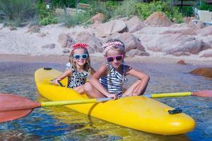 små söta flickor njuter av kajakpaddling på gul kajak
