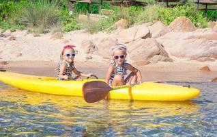 små bedårande flickor som njuter av kajakpaddling på gul kajak