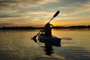 kvinna kajaker vid solnedgången foto
