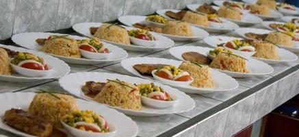 rader med tallrikar med ris och kyckling foto