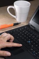hand med bärbar dator och kaffekopp foto