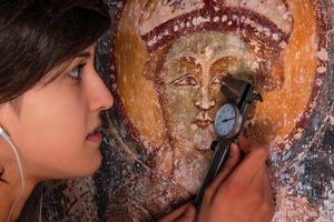 flicka som mäter för renovering en forntida fresco. foto