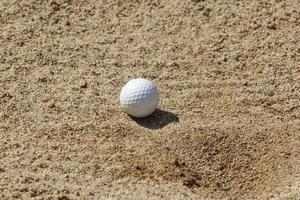 golfboll i en sandfälla foto
