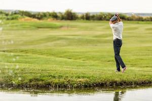 ung man spelar golf foto